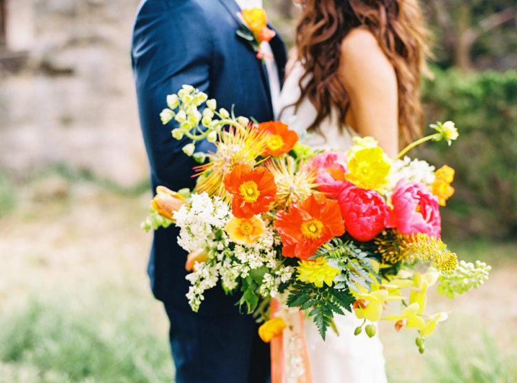 The bride was rocking a super bold bouquet in pink, yellow, red and orange