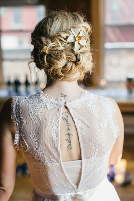 braided messy updo with a beaded flower hairpiece