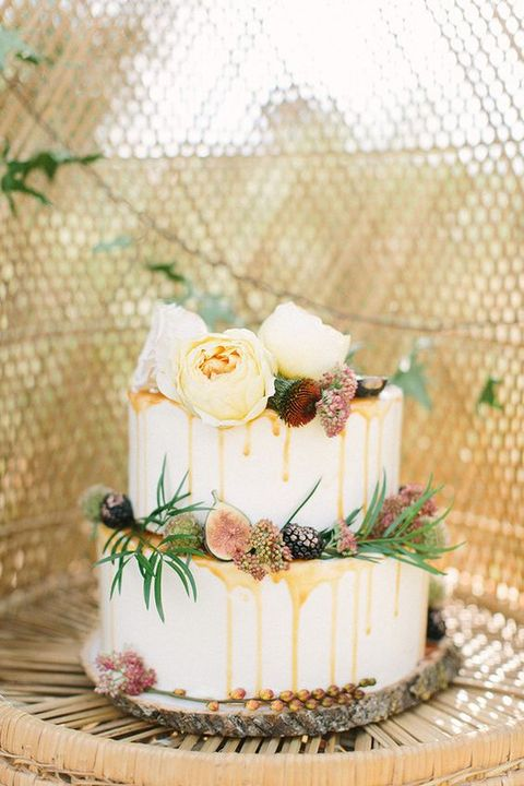 frosted wedding cake with caramel drip, figs, gilded blackberries, fresh flowers and greenery