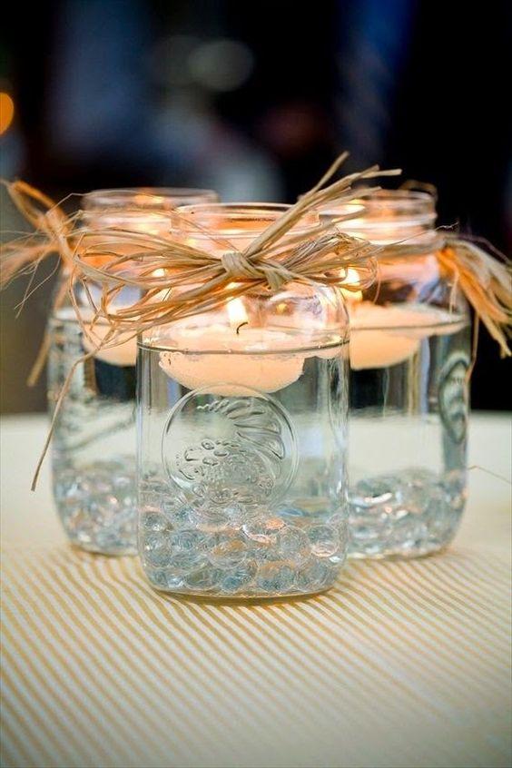 Gläser mit schwimmenden Kerzen und etwas Stroh für eine Rustikale Atmosphäre