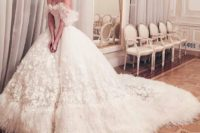 10 tulle off the shoulder wedding ball gown heavily embellished with appliqued flowers and a border of ostrich feathers around the hem, including the train