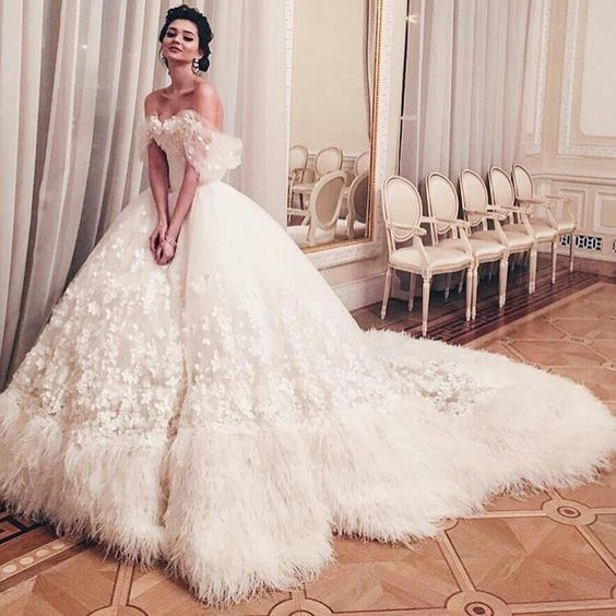 tulle off the shoulder wedding ball gown heavily embellished with appliqued flowers and a border of ostrich feathers around the hem, including the train