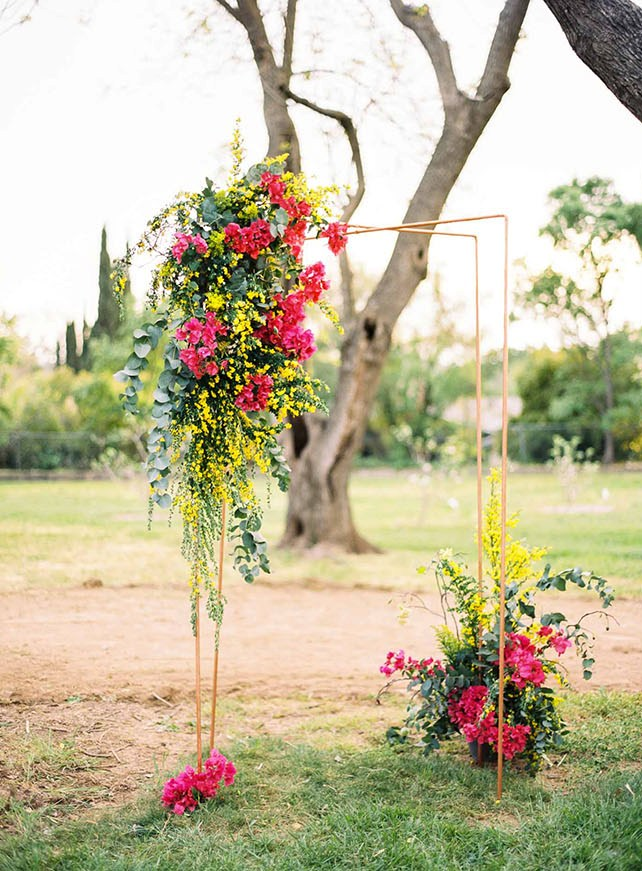 I also like the wedding arch with bold yellow and fuchsia flowers on the corner