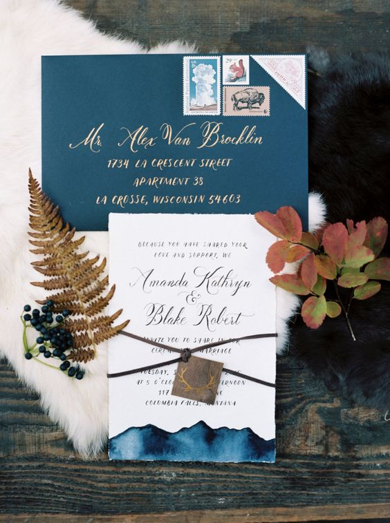 a blue envelope with gold calligraphy and an invite with blue watercolor touches and an antler tag