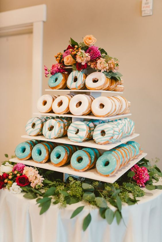 colorful glaze donut tower displayed with flowers and greenery