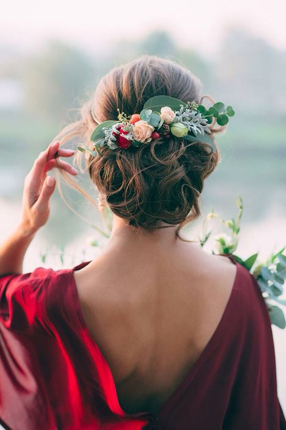 curly wedding updo topped with a fresh flower and greenery headpiece