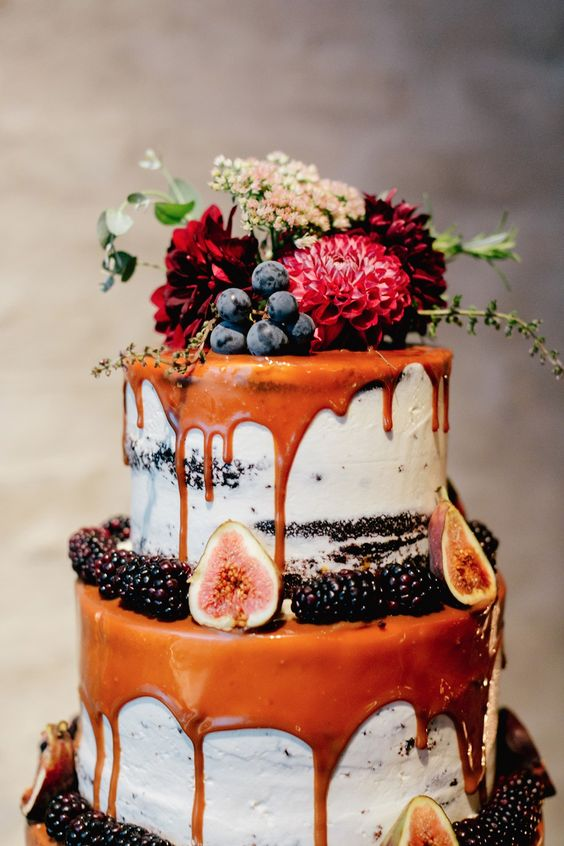 semi naked wedding cake with caramel drip, figs, blackberries, grapes and fresh flowers