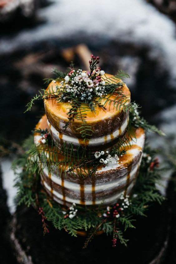 semi naked wedding cake with caramel drip, ferns and fresh flowers
