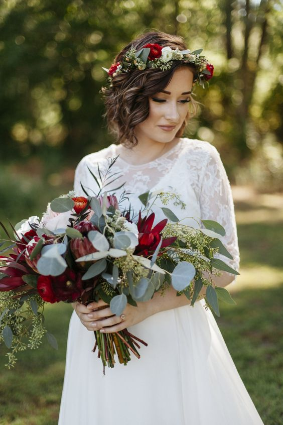 a wedding bouquet of eucalyptus, red ranunculus and proteas