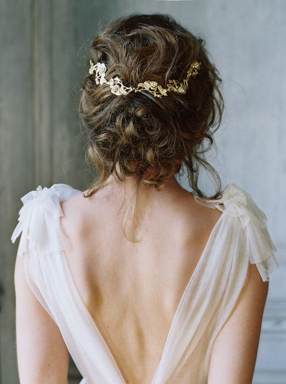 messy curly wedding updo with a gold and rhinestone hair vine