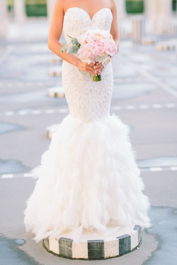 strapless sweetheart neckline mermaid wedding dress with embellishments and a feather skirt