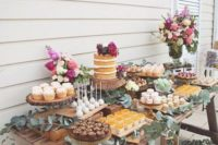 14 a rustic wooden table for a dessert bar, wooden boxes with candles and eucalyptus for decor