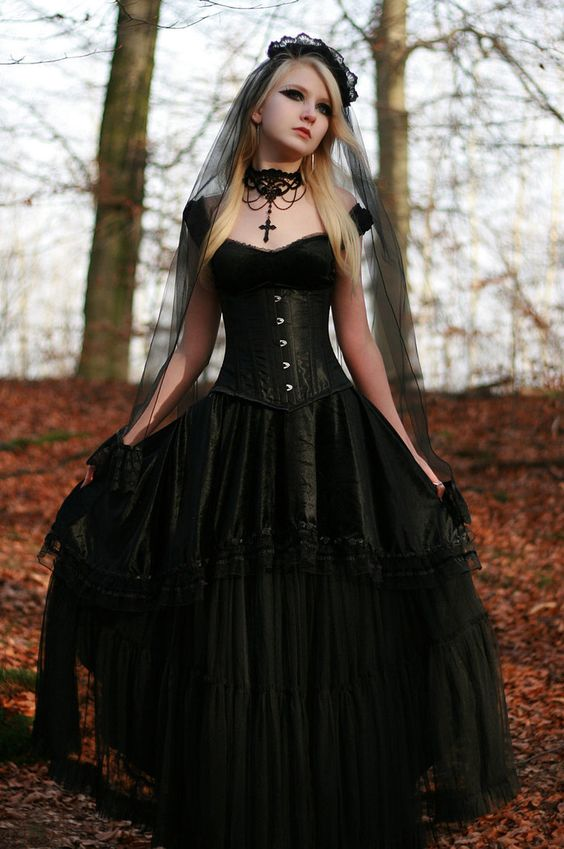 vintage corset wedding dress, a black veil with a lace edge and a statement necklace for a vintage-inspired bride