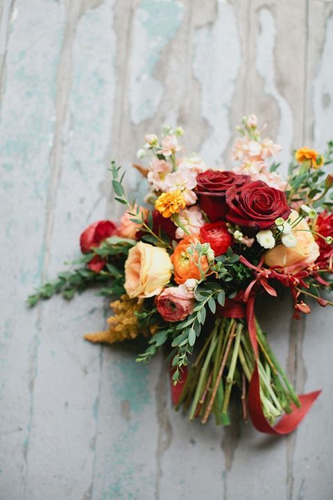 a bouquet with red roses, orange ranunculus and greenery