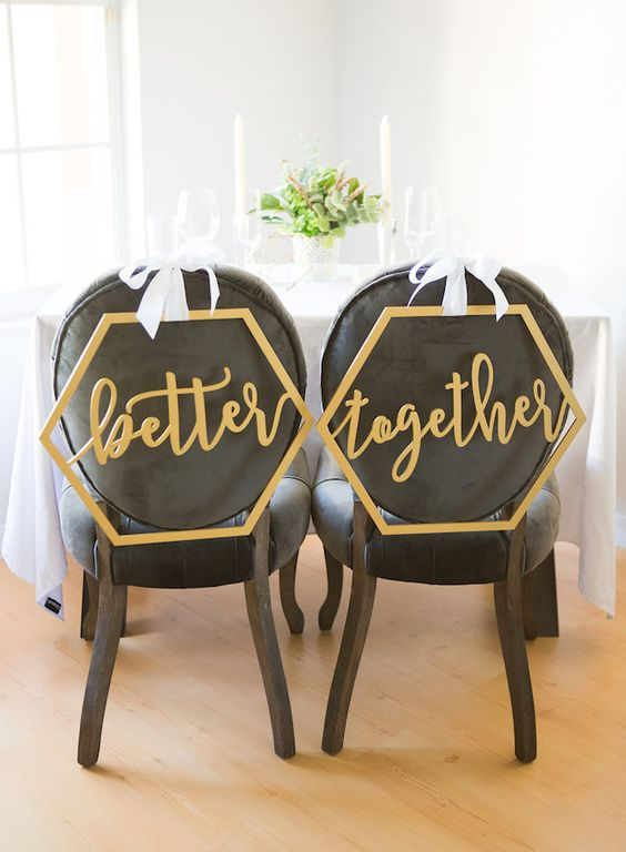 a gold calligraphy hexagon wedding chair signs contrast black chairs