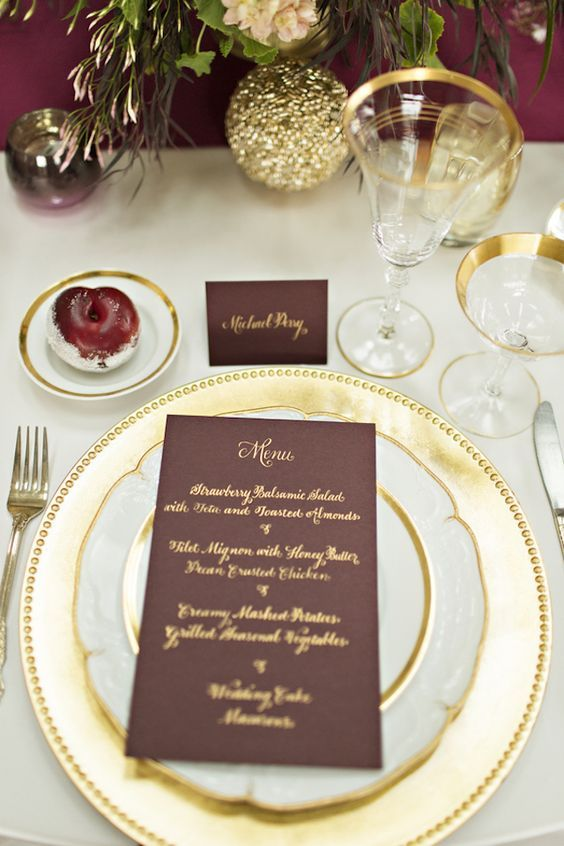 a gold charger and flatware, gilded edge plates and glasses, cards and menus with gold calligraphy