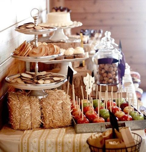a rustic dessert bar with hay, metal stands and seasonal fruits