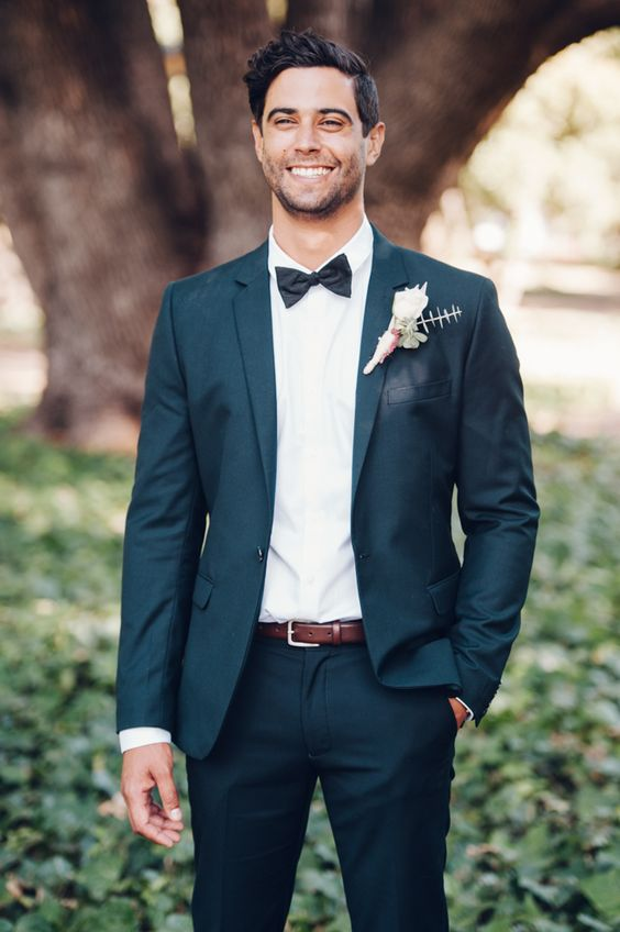 a dark grey wedding suit with a white shirt, a black bow tie