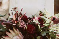 16 a lush wedding bouquet with eucalyptus, burgundy dahlias and a king protea
