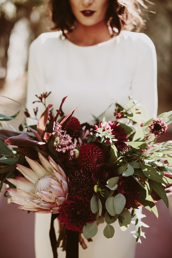 a lush wedding bouquet with eucalyptus, burgundy dahlias and a king protea