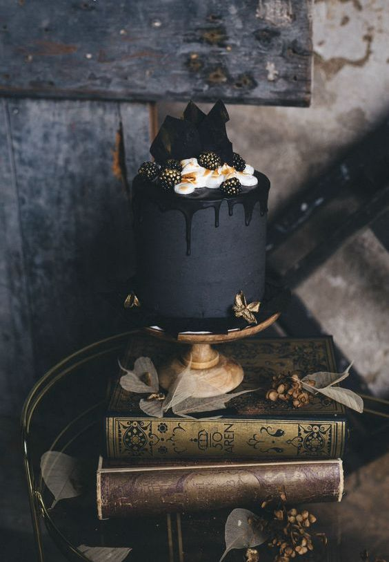 a matte black wedding cake with black chocolate drip, cream and gilded blackberries is great for Halloween