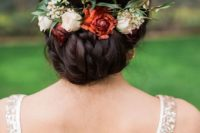 17 braided low updo with foliage and fall flowers for a relaxed bridal look