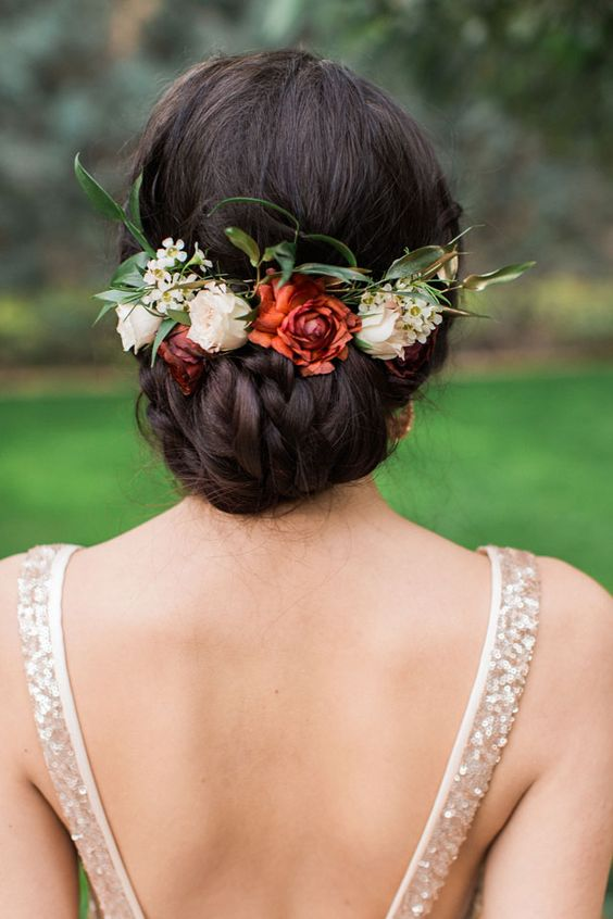 braided low updo with foliage and fall flowers for a relaxed bridal look