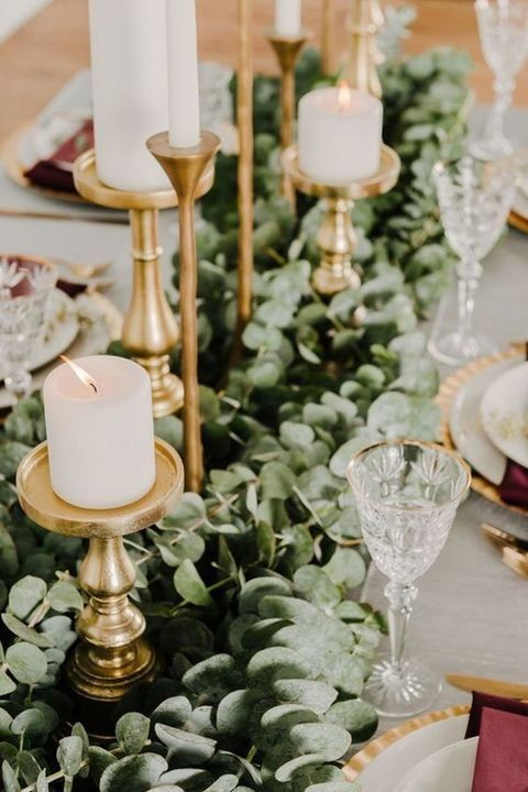 elegant gold candle holders with white candles and a lush eucalyptus garland