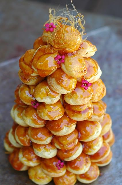 a caramel topped croquembouche with small fresh flowers