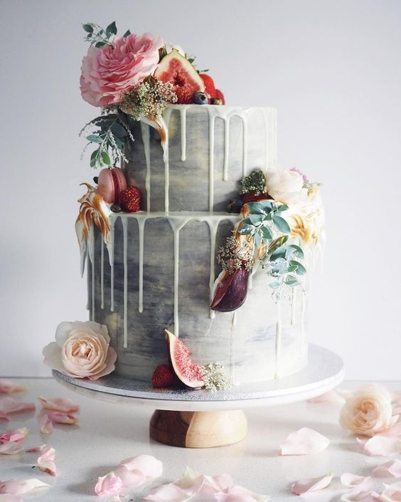grey wedding cake with white chocolate drip, figs, raspberries and fresh blooms