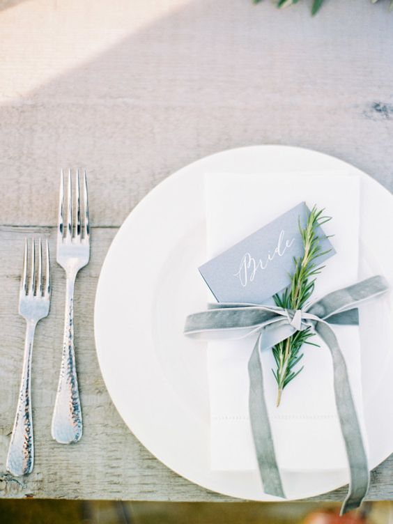 a minimalist table setting with a white napkin and a dusty blue velvet ribbon