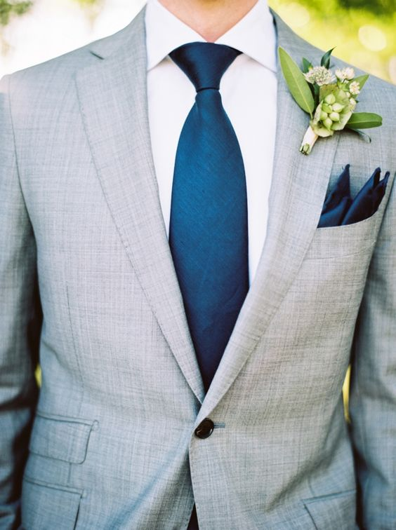a light grey wedding suit with a wide blue tie and a white shirt looks fresh
