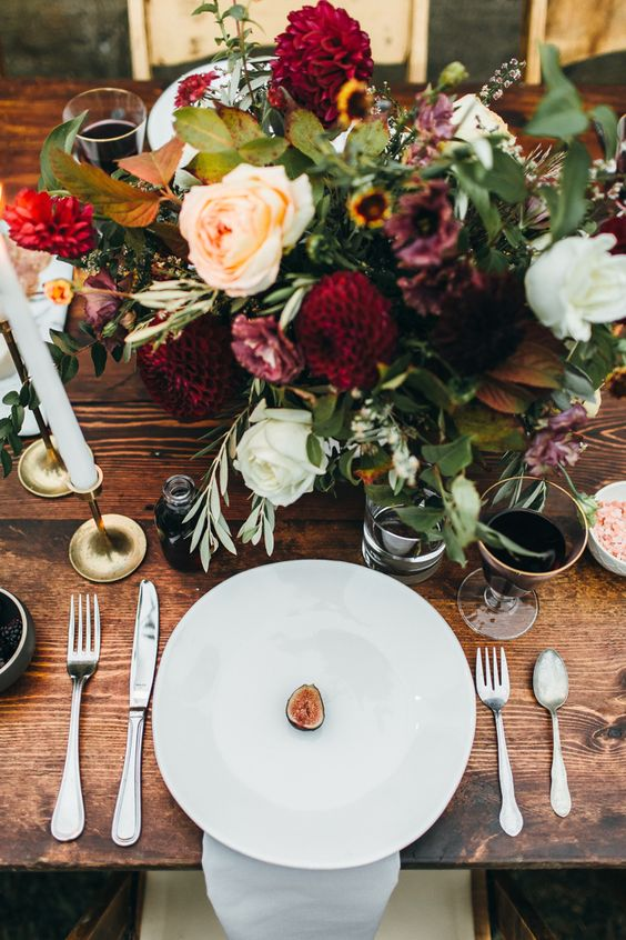 a fall table setting with a textural floral centerpiece and candles