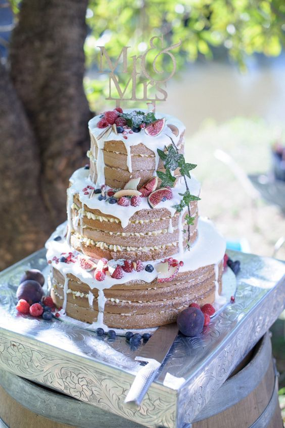 rustic naked wedding cake with white chocolate drip, figs, raspberries, blueberries