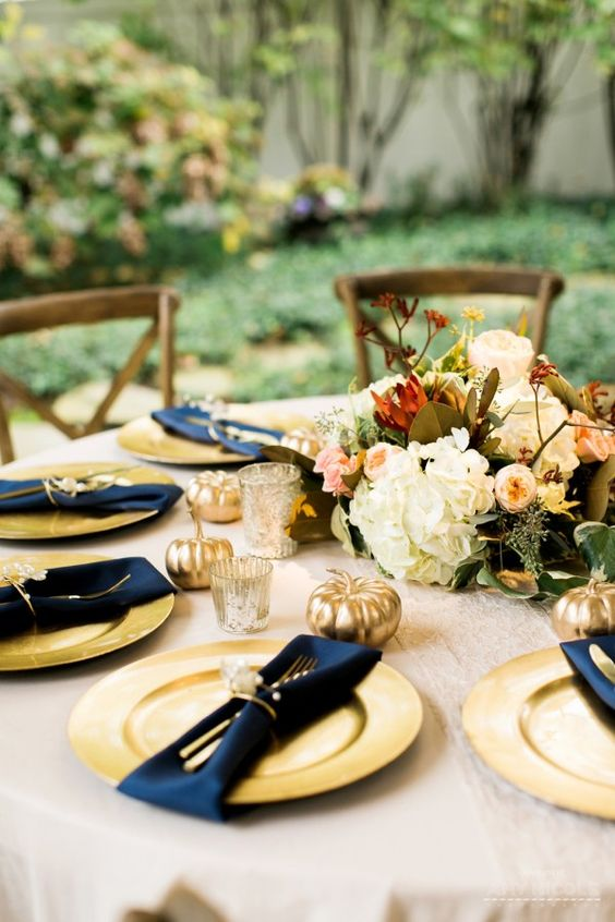 a fall tablescape with gold chargers, navy napkins and gilded pumpkins