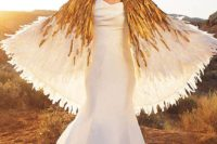 23 modern fit and flare wedding dress with a train and a white and gold feather cape attached