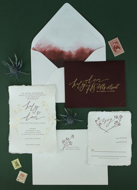 neutral calligraphy wedding stationary and a burgundy envelope with gold letters