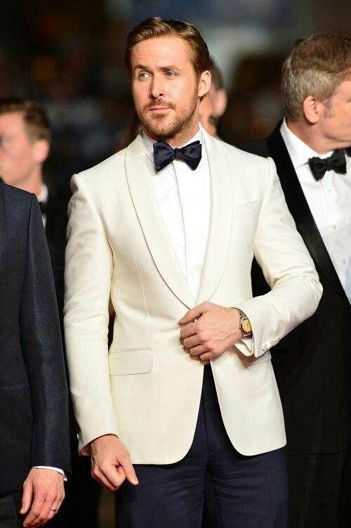 Ryan Gosling rocking an ivory dinner jacket and navy tuxedo pants