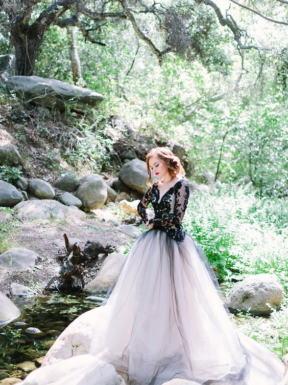 a black lace bodice with long sleeves and a deep V-neck and a white tulle skirt covered with a black tulle layer