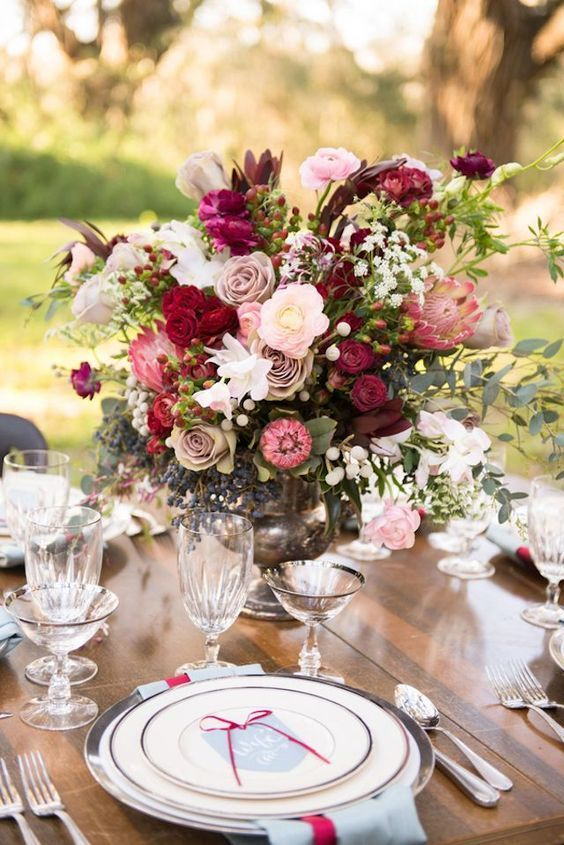 a table setting with a lush floral centerpiece with dusty pink and red roses