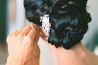 24 twisted low bun with a rhinestone hairpiece on one side