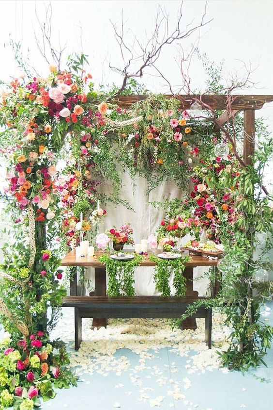 a table setting with lush florals and greenery around is very garden-like