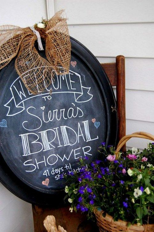 an oval chalkboard sign with a burlap bow