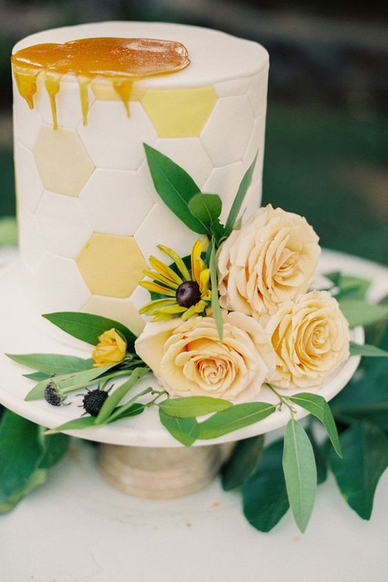 a hexagon wedding cake topped with honey and with fresh flowers and greenery