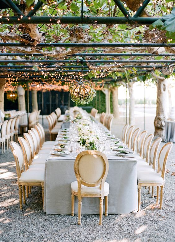 an elegant fall garden reception in dove grey and cream, with leaves and lights above