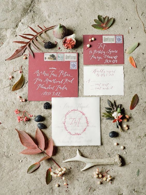 berry-hued wedding envelopes and neutral invites with wreath prints
