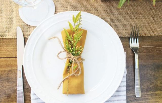 farm table setting with a burlap table runner and a mustard napkin with twine and greenery