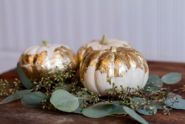 gold leaf pumpkins and eucalyptus for a wedding centerpiece