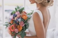 26 twisted low updo with large orange blooms for a romantic fall-inspired look