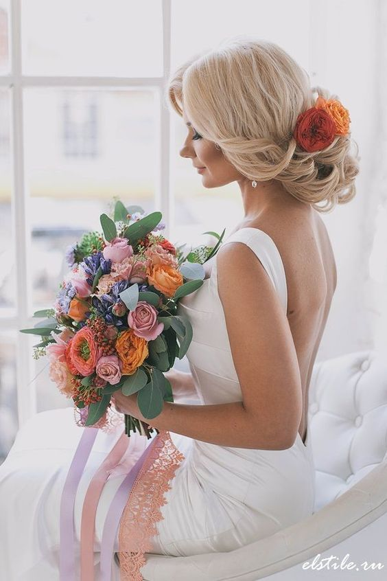 twisted low updo with large orange blooms for a romantic fall-inspired look